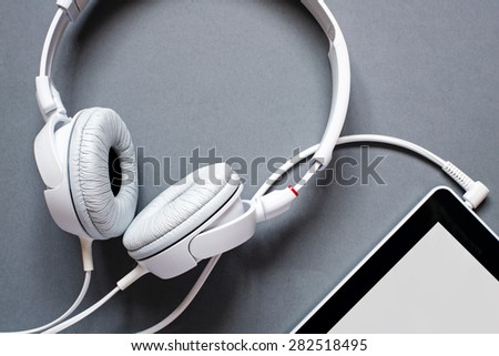 High Angle View of Modern White Audio Headphones with Cord Plugged Into Tablet Computer Jack on Grey Desk Background