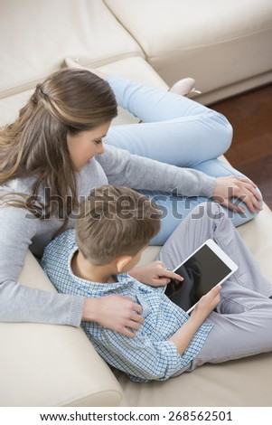 High angle view of mother and son using tablet PC on sofa - stock photo
