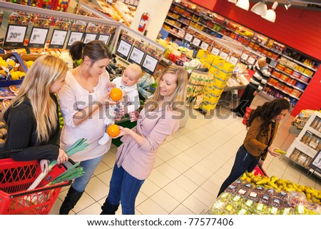 High angle view of mother carrying child with friends shopping in supermarket - stock photo