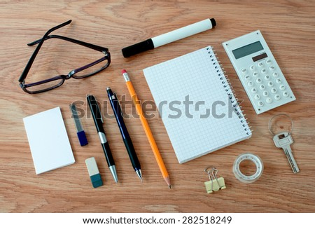 High Angle View of Office or School Supplies Arranged Neatly Around Notebook with Blank Page on Wooden Desk Surface - stock photo