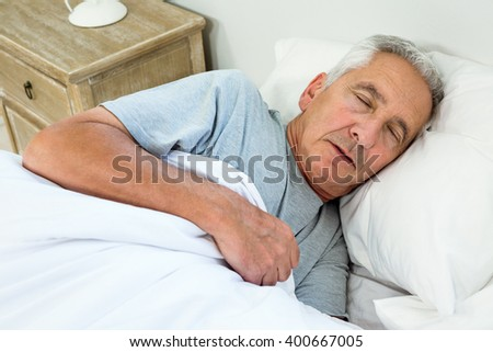 High angle view of old man sleeping on bed at home - stock photo