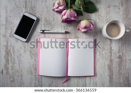 High angle view of open empty notebook, mobile phone, cup of coffee and bouquet of roses on white wooden table