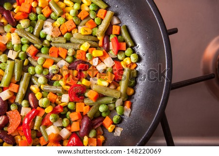 High angle view of pan with vegetables on kitchen stove  - stock photo