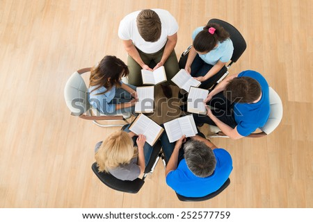 High Angle View Of People Reading Bible Together - stock photo