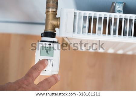 High Angle View Of Person's Hand Adjusting Temperature On Thermostat - stock photo