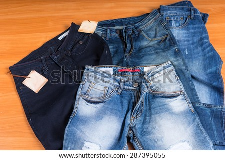 High Angle View of Pile of Front Facing Blue Jeans in Various Color Washes and Styles on Wooden Surface Background - stock photo