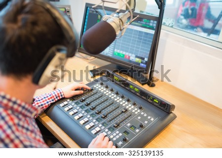 High angle view of radio host operating sound mixer on table in studio - stock photo
