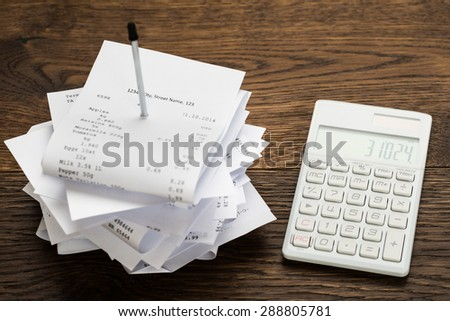 High Angle View Of Receipts With Calculator On Wooden Table - stock photo