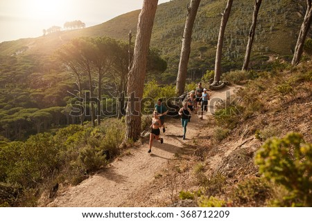 High angle view of running club group training on mountain trails. Group of fit athletes running on mountain path. - stock photo