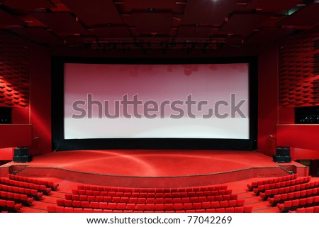 High-angle view of screen and rows of comfortable red chairs in illuminate red room cinema - stock photo
