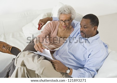 High angle view of senior African American couple looking at bills while sitting on sofa - stock photo