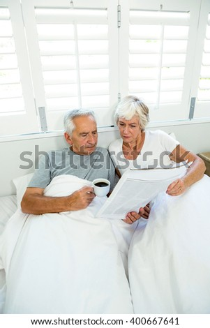High angle view of senior couple reading newspaper while relaxing on bed - stock photo
