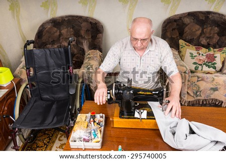 High Angle View of Senior Man at Home Using Old Fashioned Manual Sewing Machine to Mend Pants, in Living Room with Wheelchair Close By - stock photo
