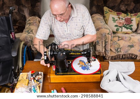 High Angle View of Senior Man Working on Needle Point Wall Hanging Using Old Fashioned Manual Sewing Machine at Home in Living Room - stock photo