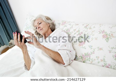 High angle view of senior woman using smart phone in bed at home - stock photo