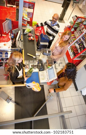 High angle view of shop assistant with customer in supermarket - stock photo