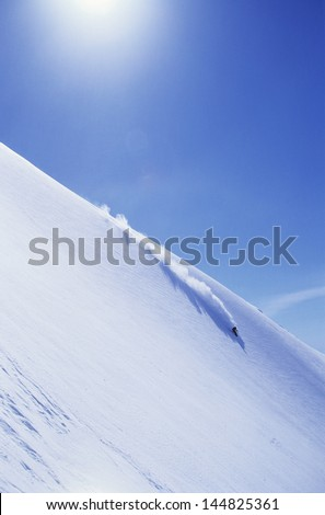 High angle view of skier skiing on mountain slope - stock photo