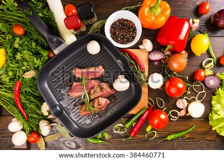 High Angle View of Sliced Rare Roast Beef Sizzling on Hot Cast Iron Frying Pan Surrounded by Fresh Ingredients - Colorful Vegetables, Fresh Herbs and Seasonings - stock photo