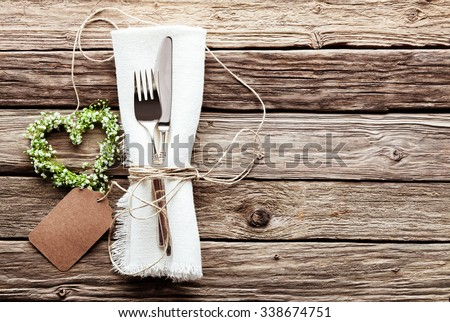 High Angle View of Small Heart Shaped Greenery Wedding Wreath at Table Setting with Silver Knife and Fork Tied with String to Fringed White Napkin with Blank Tag on Rustic Wooden Table Surface - stock photo