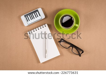 High angle view of smart phone, blank paper or notebook, pen, coffee mug and glasses on wooden surface. Copy space available. Mockup concept.  - stock photo