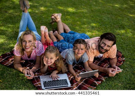High angle view of smiling family using technologies while lying on grass in yard - stock photo