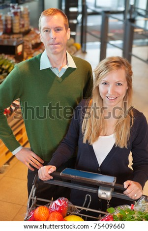 High angle view of smiling woman looking at camera while shopping with man in store