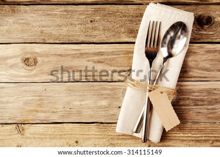 High Angle View of Spoon and Fork Tied on a White Napkin with Empty Tag, Placed on Wooden Table with Copy Space. - stock photo