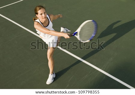 High angle view of sporty female playing on tennis court - stock photo