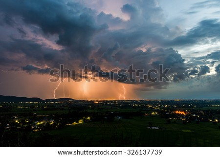 High angle view of Storm and lightning over villages - stock photo