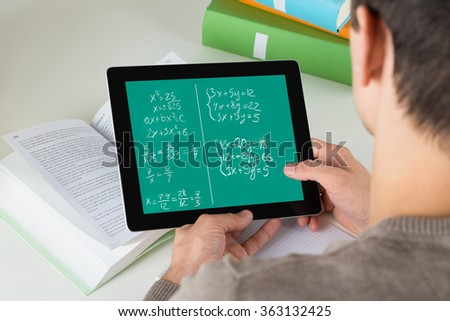 High angle view of student learning mathematical equations on digital tablet while studying at desk - stock photo
