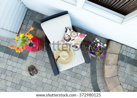 High Angle View of Sun Hat Resting on Comfortable Patio Chair with Floral Pattern Cushion and Framed by Colorful Flowers - Small Side Table with Glass of Red Wine and Shoes on Luxury Stone Patio - stock photo
