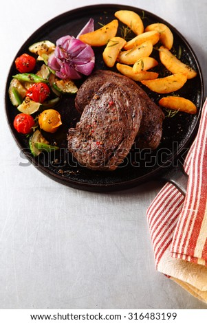 High Angle View of Tasty Roasted Beef Steak with Grilled Veggies on Iron Cast Skillet, Served on the Table for Dinner. - stock photo