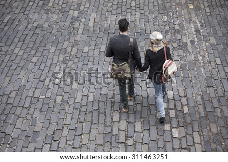 High angle view of the back of a couple walking down the street. Young man and woman walking together. - stock photo