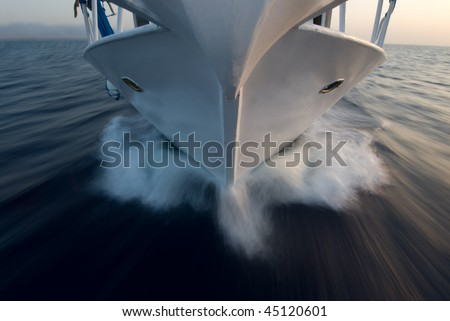 High angle view of the bow of a small motor boat moving over the surface of a flat sea. - stock photo