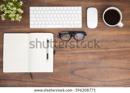 High angle view of the desk of a writer seen from above, including a notepad, a keyboard and some glasses - stock photo