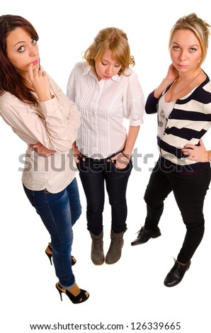 High angle view of three attractive young woman having a discussion pausing for a moment to look up at the camera isolated on white - stock photo