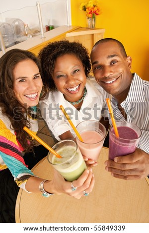 High angle view of three people at a cafe drinking frozen beverages. Vertical shot. - stock photo