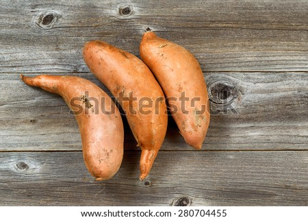 High angle view of three unclean yams on rustic wood. Layout in horizontal format. - stock photo