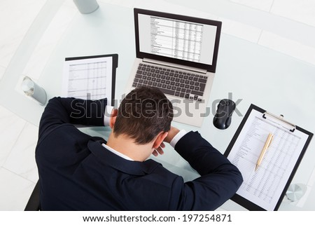 High angle view of tired businessman sleeping while calculating expenses at desk in office - stock photo