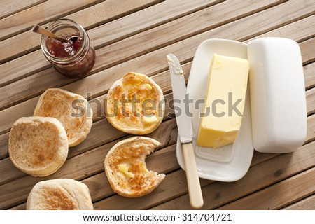 High Angle View of Toasted English Muffins with Butter and Jam on Top of Wooden Table - stock photo