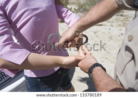 High angle view of traffic cop arresting young woman - stock photo