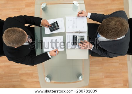 High Angle View Of Two Businessman Calculating Documents Using Calculator - stock photo