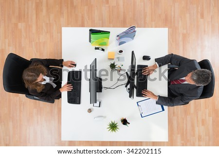 High Angle View Of Two Businesspeople Working On Computers In Office - stock photo