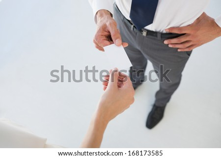 High angle view of two executives exchanging business card - stock photo