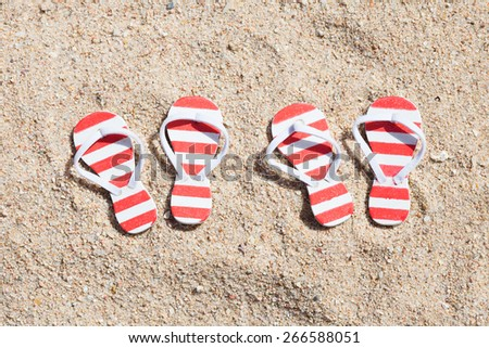 High Angle View Of Two Pairs Striped Flip-flops On Beach - stock photo