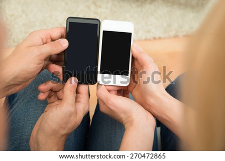 High Angle View Of Two People Holding Mobile Phones - stock photo