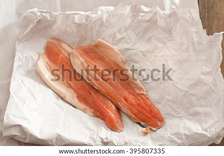 High angle view of two pink uncooked fish fillets displayed on white wrinkled paper - stock photo
