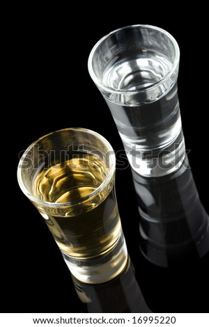 High angle view of two shots of tequila isolated on a black background - stock photo