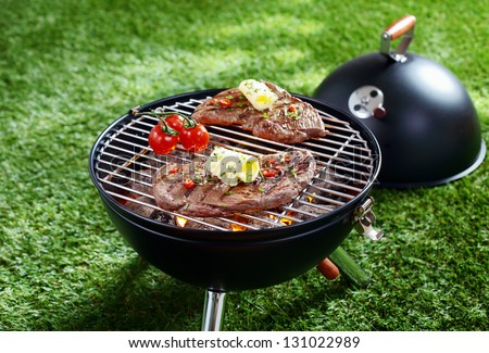 High angle view of two succulent steaks cooking on a barbecue over the hot coals on a green lawn outdoors - stock photo