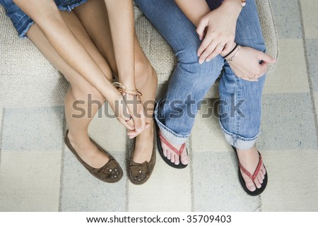 High angle view of two teenage girls sitting on a couch